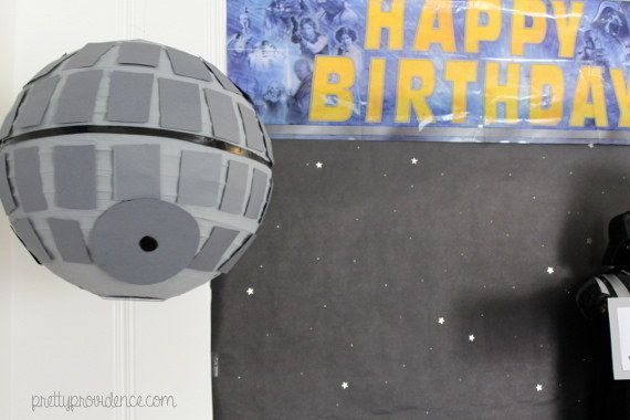 Turn a paper lantern into the Death Star with gray spray paint, black tape, and a few pieces of cardboard.